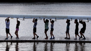 Rowers carry a shell after pulling if from the Hudson River during rowing summer camp at the Albany Rowing Center on Friday, July 10, 2015, in Albany, N.Y. (AP Photo/Mike Groll)