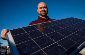 Curtis Buxton, a project manager at Skyfire Energy Inc., who was forced to look for new employment after being downsized out of the oil and gas industry, poses with solar panels, in Calgary on Monday, Jan. 25, 2016. (Jeff McIntosh/THE CANADIAN PRESS)