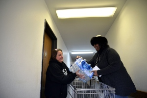 Lisa Epstein, right, the principal of Henry H. Lee Elementary School in Chicago, lifts a case of water with Flint resident Vanessa Pringle on Saturday, Feb. 6, 2016 at the Slidell Senior Residence Apartments in Flint. (Rachel Woolf/The Flint Journal/ MLive.com via AP)