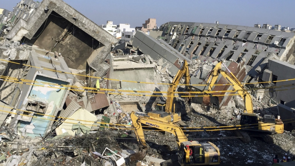 Rescue workers using excavators continue to search the rubble of a collapsed building complex in Tainan, Taiwan on Tuesday, Feb. 9, 2016. (AP / Annie Ho)