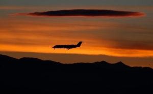 As the suns sets behind the mountains, a passenger plane comes in for a landing at Denver International Airport late Monday, Feb. 8, 2016, in Denver. (AP/David Zalubowski)