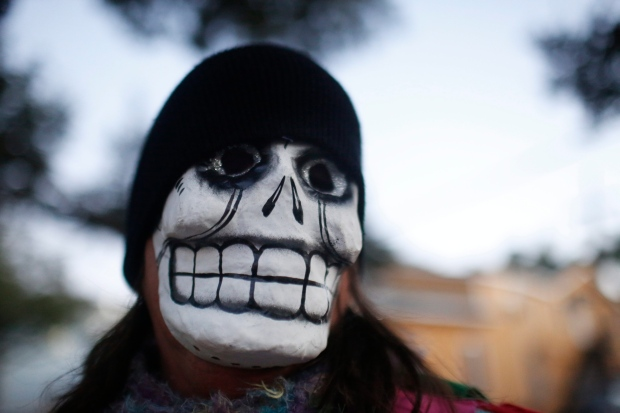 A parade-goer walks the streets with the North Side Skull & Bone Gang, during the wake up call for Mardi Gras, Tuesday, Feb. 9, 2016, in New Orleans. (AP / Brynn Anderson)