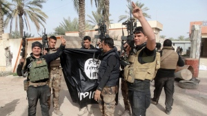 In this Tuesday, Jan. 19, 2016 photo, Iraqi security forces celebrate as they hold a flag of the Islamic State group they captured in Ramadi. (AP Photo)