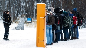Migrants receive instructions from a Norwegian police officer at the Storskog boarder crossing station near Kirkenes, in Norway, on Monday, Nov. 16, 2015. (Cornelius Poppe, NTB scanpix via AP)