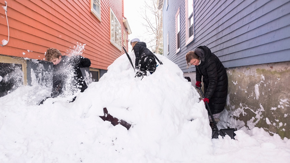 Candace Leinwand, right, digs her buried car out of snow with her sons Elijah, left, and Ryder following a major winter storm, in Halifax on Tuesday, Feb. 9, 2016. (Darren Calabrese / THE CANADIAN PRESS)