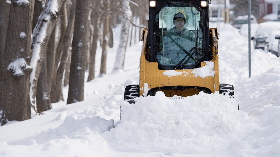 A plow clears sidewalks in Halifax on Tuesday, Feb. 9, 2016. (Andrew Vaughan / THE CANADIAN PRESS)