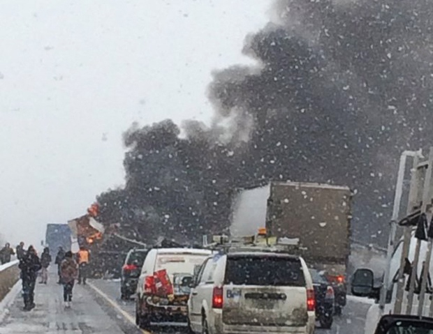 Smoke billows from a truck following a collision on Highway 401 west of Woodstock on Wednesday, Feb. 10, 2016. (Sean Rea / Twitter)