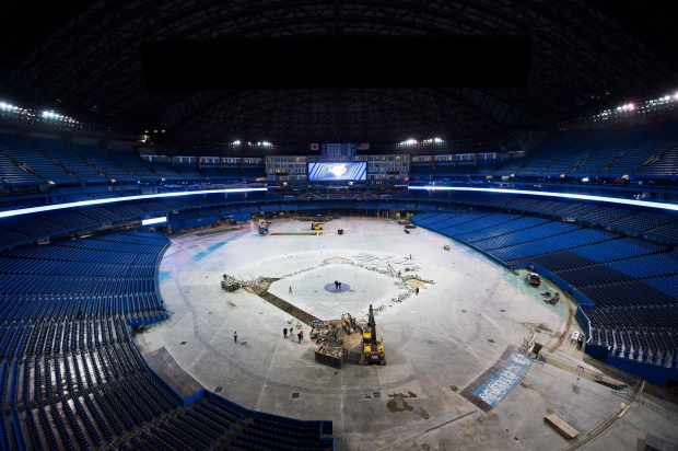 Construction workers hammer out concrete as they install the new dirt infield for the Toronto Blue Jays upcoming season at the Rogers Centre in Toronto on Wednesday, February 10, 2016. (Nathan Denette / THE CANADIAN PRESS)