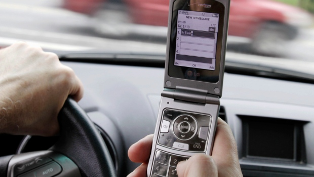 A person texts while driving in Brunswick, Maine, on Sept. 20, 2011. (AP Photo/Pat Wellenbach)