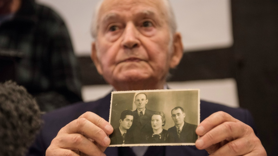 Auschwitz concentration camp survivor Leon Schwarzbaum presents a photograph showing himself, left, next to his uncle and parents who all died in Auschwitz, during a news conference in Detmold, Germany, Wednesday, Feb. 10, 2016. (Bernd Thissen / dpa)