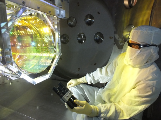 A LIGO optics technician inspects a mirror by illuminating its surface with light at a glancing angle. (Caltech / MIT / LIGO Lab / Matt Heintze)