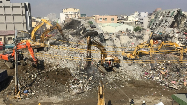 Rescue teams continue to use heavy excavation machinery to dig through the rubble of a collapsed building complex in Tainan, Taiwan, Thursday, Feb. 11, 2016. (AP Photo/Johnson Lai)