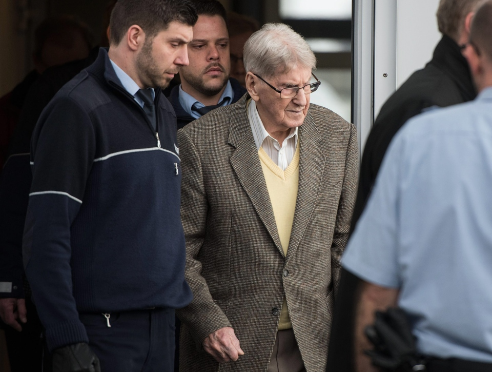 94-year-old former SS guard at the Auschwitz death camp Reinhold Hanning, centre, leaves the building after the opening of his trial in Detmold, Germany, Thursday, Feb. 11, 2016. (Bernd Thissen / AP)