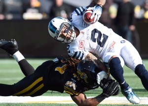 Toronto Argonauts' Chad Owens (2) goes down as he's sacked by Hamilton Tiger-Cats' Taylor Reed (44) during first half CFL Eastern Division Semifinal football action, in Hamilton, Ont., on Sunday, Nov. 15, 2015. (Frank Gunn / THE CANADIAN PRESS)