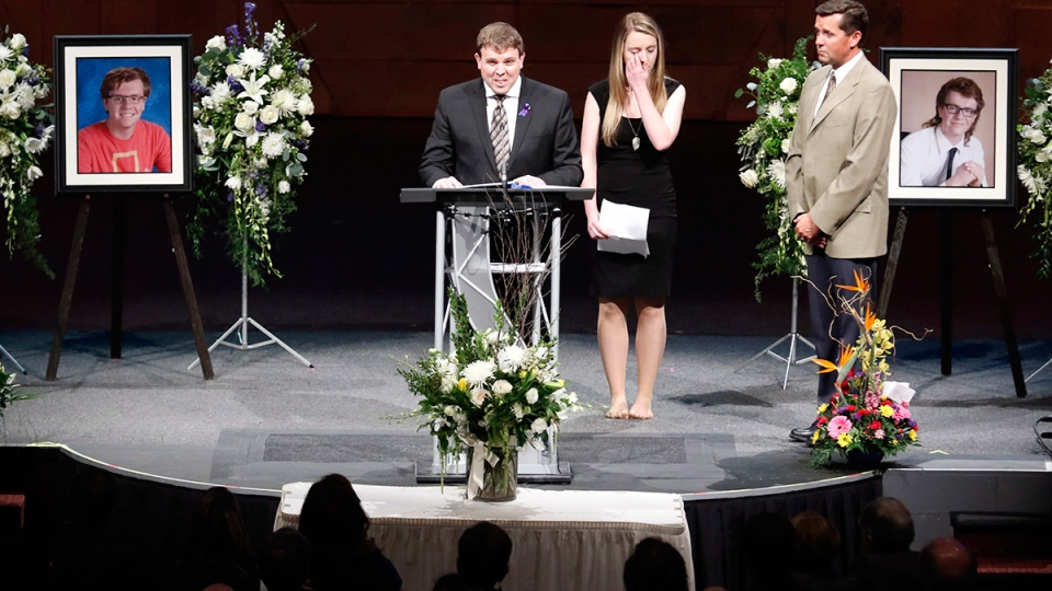 Sister Katie Caldwell, centre, wipes a tear and family pastor Glenn Nudd, right, looks on as father Jason Caldwell delivers the eulogy at a memorial service for twin brothers Evan and Jordan Caldwell, killed in a Saturday bobsled track incident at Canada Olympic Park, in Calgary, on Thursday, Feb. 11, 2016. (Larry MacDougal / THE CANADIAN PRESS)