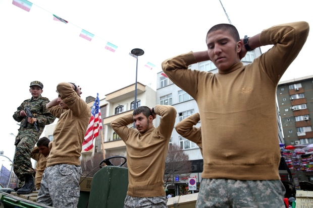 Members of Iranian Basij paramilitary force re-enact the January capture of U.S. sailors by the Revolutionary Guard in the Persian Gulf, in a rally commemorating the 37th anniversary of Islamic Revolution in Tehran, Iran, Thursday, Feb. 11, 2016. (AP Photo/Ebrahim Noroozi)