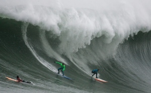 In this Jan. 12, 2008, file photo, three competitors surf a giant wave during the Mavericks surf contest in Half Moon Bay, Calif. (AP / Ben Margot)
