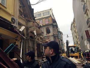 Police officers look up as firefighters investigate the collapse of two old buildings in the Beyoglu district in Istanbul, Friday, Feb. 12, 2016. (AP Photo/Dominique Soguel)
