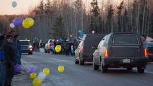 Hundreds of resident's line the road leading into the small town of La Loche, Sk. Monday, Jan. 25, 2016 to welcome two brothers killed last Friday. (THE CANADIAN PRESS/Jonathan Hayward)
