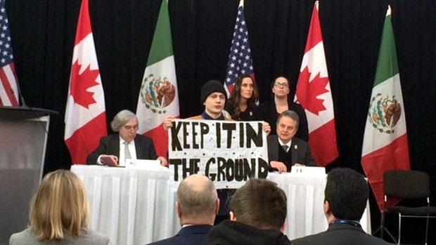 A protester interrupts a news conference announcing a clean energy agreement between Canada, the United States and Mexico in Winnipeg, on Feb. 12, 2016.