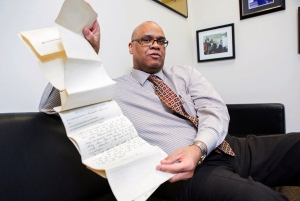 In this Thursday, Feb. 11, 2016 photo, James Sledge, an executive officer at the Cook County Medical Examiner's office in Chicago, holds one of the original autopsy reports from the infamous Valentine's Day massacre 87 years ago. (James Foster/Chicago Sun-Times via AP)