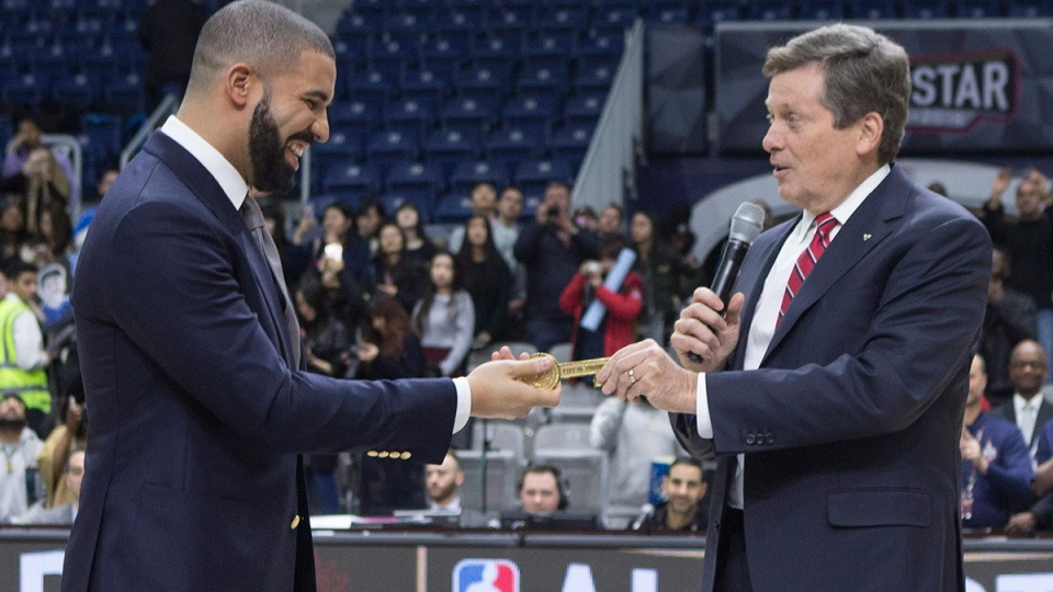 Toronto's Mayor John Tory, right, hands Drake the key to the city ahead of the celebrity all-star game in Toronto on Friday, Feb. 12, 2016. (Chris Young / THE CANADIAN PRESS)