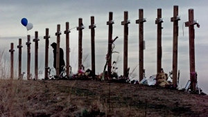 This April 28, 1999 file photo shows a woman standing among 15 crosses posted on a hill above Columbine High School in Littleton, Colo., in remembrance of the 15 people who died during a school shooting on April 20, 1999. (AP Photo / Eric Gay, file)