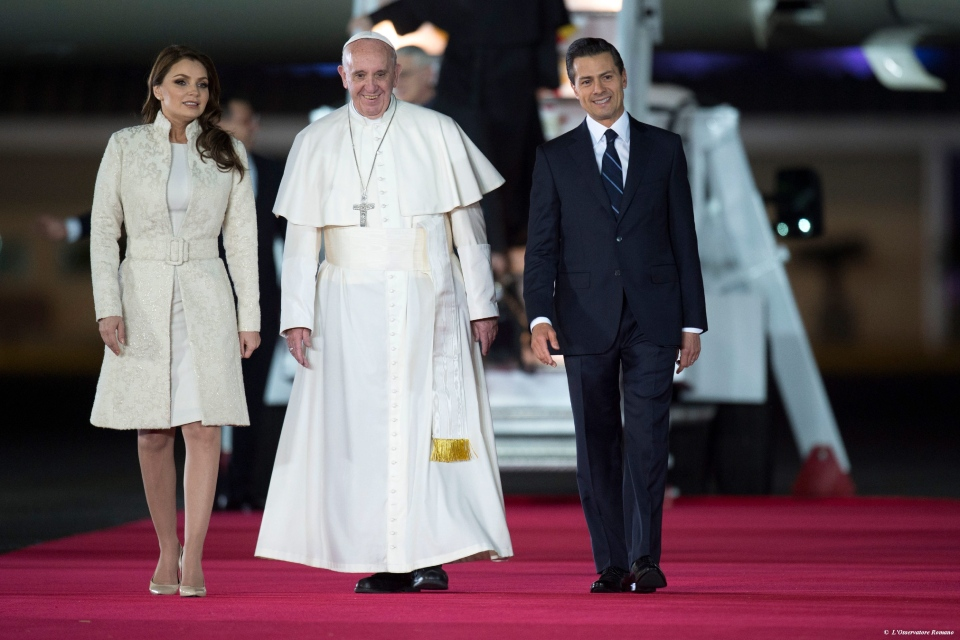 In this photo taken on Friday, Feb. 12, 2016, Pope Francis poses with Mexico's President Enrique Pena Nieto, right, and first lady Angelica Rivera upon his arrival to the Benito Juarez International Airport in Mexico City. (L'Osservatore Romano/Pool Photo via AP)