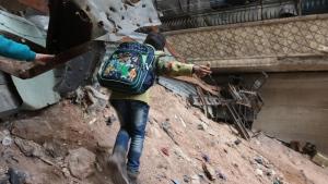 A child navigates through rubble and barbed wire in Aleppo, Syria, Thursday, Feb. 11, 2016. (Alexander Kots/Komsomolskaya Pravda via AP)