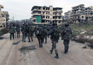 This Tuesday, Jan 12, 2016, file photo released by the Syrian official news agency SANA, shows Syrian government troops and allied militiamen walk inside the key town of Salma in Latakia province, Syria. (SANA via AP, File)