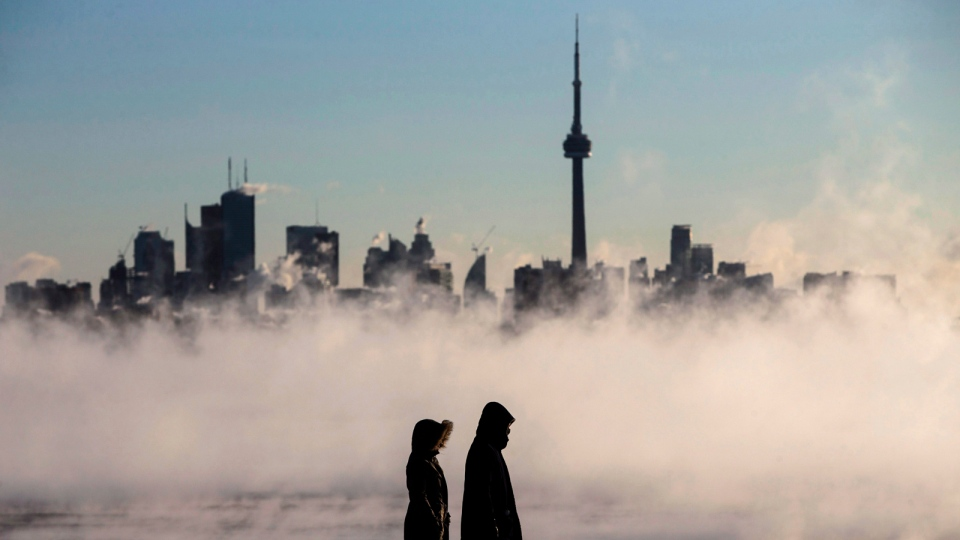 Steam rises as people look out on Lake Ontario in front of the skyline during extreme cold weather in Toronto on Saturday, Feb. 13, 2016. (Mark Blinch / THE CANADIAN PRESS)