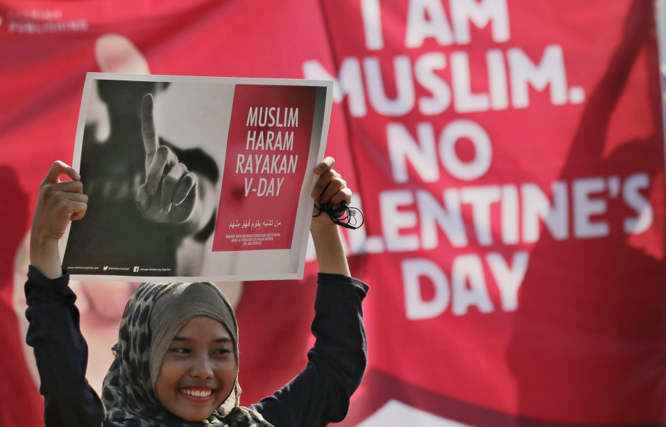 A Muslim girl displays posters 'Muslims forbidden to celebrate Valentine's Day' during a protest against Valentine's Day in Jakarta, Indonesia, Sunday, Feb. 14, 2016. (AP/Achmad Ibrahim)