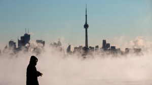 Steam rises as a man looks out on Lake Ontario in front of the skyline during extreme cold weather in Toronto on Saturday, February 13, 2016. (Mark Blinch / THE CANADIAN PRESS)