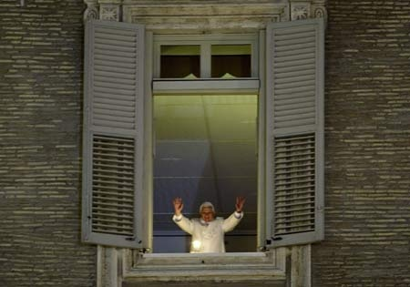 Pope Benedict XVI waves to faithful after lighting a candle from his studio window overlooking St. Peter's Square at the Vatican, on the occasion of the inauguration of the Nativity scene displayed in the square, Wednesday, Dec. 24, 2008. (AP Photo / Andrew Medichini)