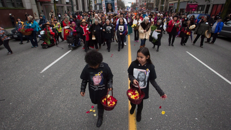 Young girls scatter flower petals on the ground while leading hundreds of people through the Downtown Eastside during the 25th annual Women's Memorial March in Vancouver, B.C., on Saturday February 14, 2015. (THE CANADIAN PRESS / Darryl Dyck)