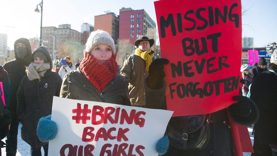 People hold up signs as they participate in the 7th annual memorial march to raise awareness for the hundreds of missing and murdered aboriginal women in Montreal, Sunday, February 14, 2016. (THE CANADIAN PRESS / Graham Hughes)
