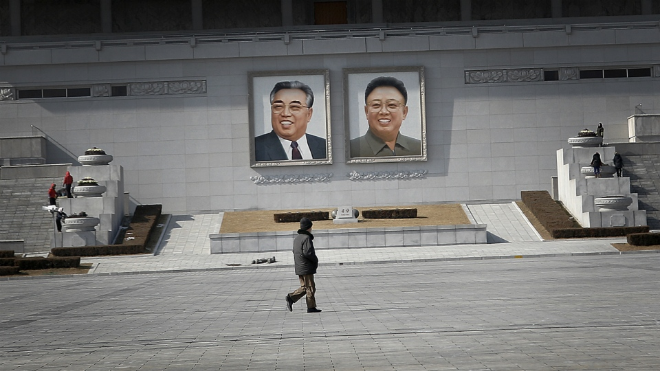 A man walks past portraits of the late North Korean leaders Kim Il Sung and Kim Jong Il, at the Kim Il Sung Square in Pyongyang, North Korea on Sunday, Feb. 14, 2016. (AP / Wong Maye-E)