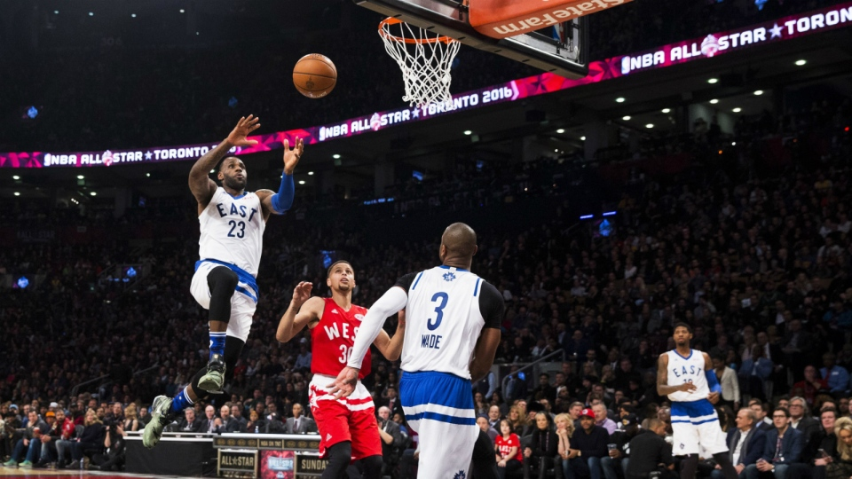 Eastern Conference's LeBron James, of the Cleveland Cavaliers, slam dunks past Western Conference's Stephen Curry, of the Golden State Warriors, during first half NBA All-Star Game basketball action in Toronto on Sunday, Feb. 14, 2016. (Mark Blinch / THE CANADIAN PRESS)