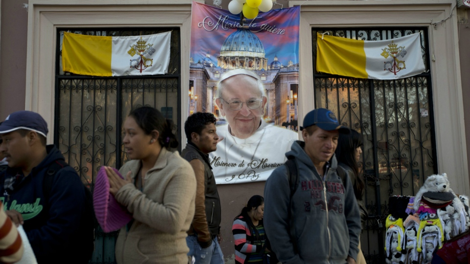 Vatican banners, balloons and a poster with an image of Pope Francis decorate a restaurant facade, located on the plaza facing the Cathedral, in San Cristobal de las Casas, Mexico on Sunday, Feb. 14, 2016. (AP / Moises Castillo)