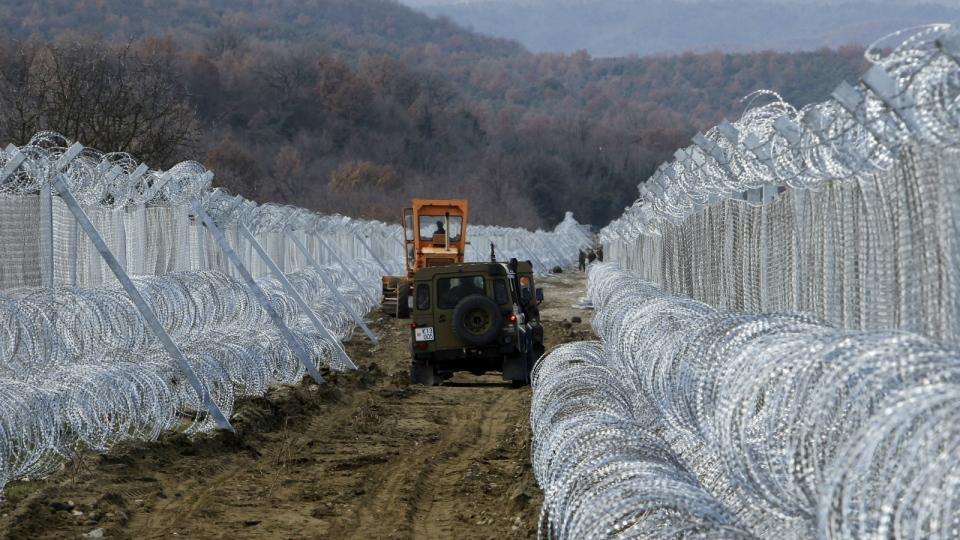 Macedonian Army vehicles move along a path between two lines of fence reinforced with razor wire, on the border line with Greece near the southern Macedonia's town of Gevgelija on Sunday, Feb. 14, 2016. (AP / Boris Grdanoski)