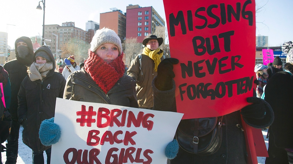 People hold up signs as they participate in the 7th annual memorial march to raise awareness for the hundreds of missing and murdered aboriginal women in Montreal, Sunday, Feb. 14, 2016. (Graham Hughes / THE CANADIAN PRESS)