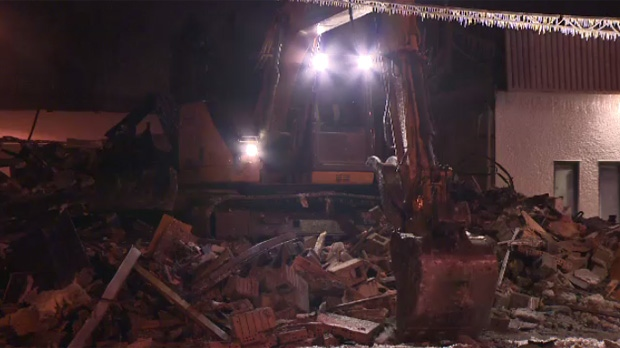 Demolition crews tore down the remnants of a building that was destroyed by a fire on Sunday.