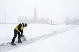 A worker shovels snow as a major winter storm hits Ottawa on Tuesday, Feb. 16, 2016. THE CANADIAN PRESS/Sean Kilpatrick