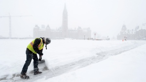 A worker shovels snow as a major winter storm hits Ottawa on Tuesday, Feb. 16, 2016. (THE CANADIAN PRESS/Sean Kilpatrick)