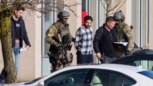 Surrey RCMP tactical officers arrest a man during a standoff after a reported bank robbery at TD Bank in Surrey, B.C., on Tuesday, Feb. 16, 2016. (Ben Nelms / THE CANADIAN PRESS)