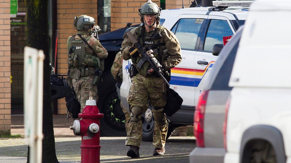Surrey RCMP tactical officers surround a TD Bank during a suspected bank robbery in Surrey, B.C., on Tuesday, Feb. 16, 2016. (Ben Nelms / THE CANADIAN PRESS)