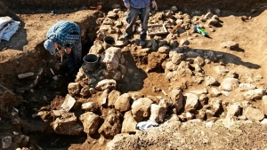 This handout photo released by the Israel Antiquities Authority on Wednesday, Feb. 15, 2016, shows work on uncovering of an ancient settlement in Jerusalem. Israeli archeologists have discovered a 7,000-year-old settlement in northern Jerusalem in what they say is the oldest discovery of its kind in the area. (Israel Antiquities Authority via AP)