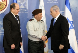 In this file photo, Israeli Prime Minister Benjamin Netanyahu, right, shakes hands with then-Major Gen. Gadi Eisenkot, during a ceremony in Jerusalem Monday, Feb. 16, 2015. On the left is Israeli Defense Minister Moshe Yaalon. (AP Photo/Sebastian Scheiner)