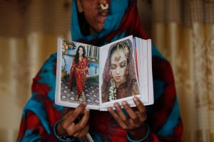 In this photo taken on Jan. 27, 2016, Sidra Kanwal shows pictures of herself before she was disfigured in an acid attack in Karachi, Pakistan. (AP Photo/Shakil Adil)