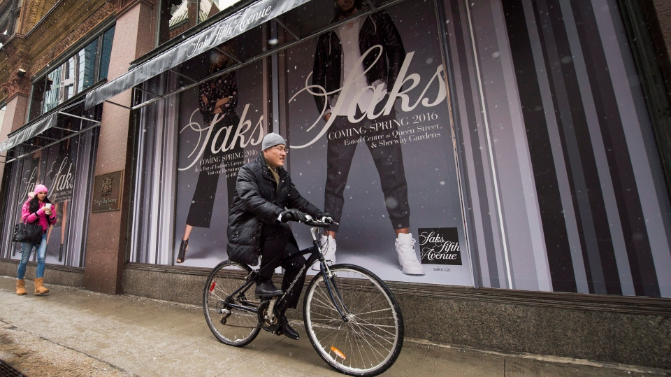 A cyclist rides past the new Saks Fifth Avenue store in downtown Toronto on Tuesday, February 16, 2016. (Nathan Denette / THE CANADIAN PRESS)